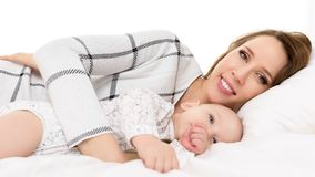 Happy young smiling mother and her baby son lying on a bed together. Mother and newborn child portrait. Stock Photo