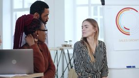 Happy young smiling multiethnic business people chat informally at modern office near finance diagram, healthy workplace. Multiracial sales professionals stock video footage