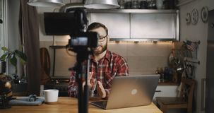 Happy young smiling tech blogger man making vlog video stream with professional camera at home kitchen slow motion. Popular successful male vlogger creating a stock video footage