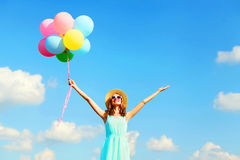 Happy young smiling woman with an air colorful balloons is enjoying a summer day over a blue sky background Royalty Free Stock Photo