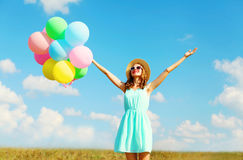 Happy young smiling woman with an air colorful balloons is enjoying a summer day over a blue sky meadow background Royalty Free Stock Photos