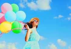 Happy young smiling woman with an air colorful balloons is having fun wearing a summer straw hat over a blue sky background. Happy young smiling woman with an Stock Photo