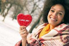 Happy young smiling woman with big red heart in winter day Stock Images