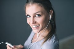 Happy young  smiling woman in earphones is listening to music with smart phone stock photography