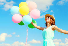 Happy young smiling woman holds an air colorful balloons is having fun wearing a summer straw hat over a blue sky background Royalty Free Stock Photography