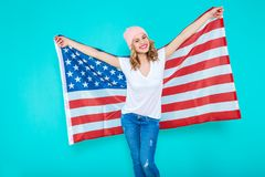 Happy young smiling woman in jeans and white Tshirt wrapped in an American flag, making peace sign and looking at camera. I love America. Happy young smiling Royalty Free Stock Photography
