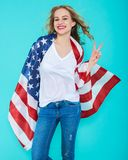 Happy young smiling woman in jeans and white Tshirt wrapped in an American flag, making peace sign and looking at camera. Stock Images