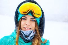 Happy young snowboarder girl in snowboard goggles. Royalty Free Stock Image