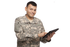 Smiling soldier working on a tablet. Happy young soldier holding a computer tablet royalty free stock photography