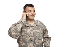 Smiling soldier talking on cell phone. Happy young soldier talking on a cell phone and looking away stock photo