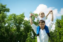 Happy young son on his shoulders the father Stock Photos