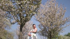 Happy young soon to be mother mom - young traveler pregnant woman enjoys her leisure free time in a park with blossoming stock footage