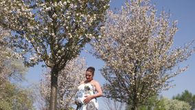 Happy young soon to be mother mom - Young traveler pregnant woman enjoys her leisure free time in a park with blossoming stock video footage