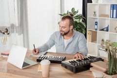 Sound producer working with mpc pads. Happy young sound producer working with mpc pads Stock Photography