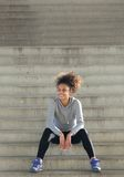 Happy young sports woman sitting on steps outdoors Stock Photography