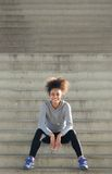 Happy young sports woman sitting steps outdoors Royalty Free Stock Photos