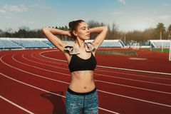 Young sports woman after workout with towel on his shoulders on the stadium after runing workout royalty free stock photos