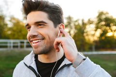 Happy young sportsman outdoors in park listening music with earphones stock photos