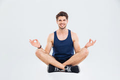 Happy young sportsman sitting in lotus pose and smiling royalty free stock photography