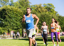Happy young sportsmen racing wit badge numbers. Fitness, sport, race and healthy lifestyle concept - group of happy teenage friends or sportsmen running marathon Stock Image