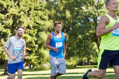 Happy young sportsmen racing wit badge numbers. Fitness, sport, race and healthy lifestyle concept - group of happy teenage sportsmen running marathon with badge Royalty Free Stock Photo