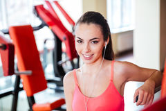 Happy young sportswoman with earphones listening to music in gym Royalty Free Stock Photos