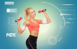 Happy young sporty woman exercising with dumbbells Royalty Free Stock Images