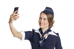 Happy young stewardess holding a smart phone isolated on white b Stock Images