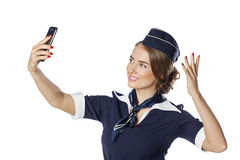 Happy young stewardess holding a smart phone isolated on white b Royalty Free Stock Images