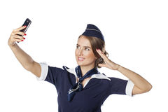 Happy young stewardess holding a smart phone isolated on white b Royalty Free Stock Photos