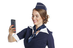 Happy young stewardess holding a smart phone isolated on white b Royalty Free Stock Photography