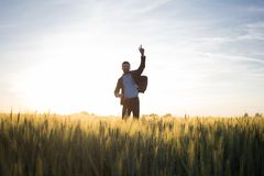 Happy young stilysh buisinesman with rised hand during the sunshine outdoors. Happy buisinesman having fun in summer fields, man in buisines suit enjoy of stock photos