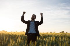 Happy young stilysh buisinesman with rised hand during the sunshine outdoors. Happy buisinesman having fun in summer fields, man in buisines suit enjoy of royalty free stock images