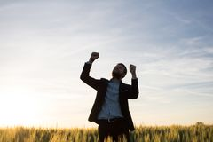 Happy young stilysh buisinesman with rised hand during the sunshine outdoors. Happy buisinesman having fun in summer fields, man in buisines suit enjoy of royalty free stock photography