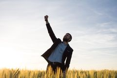 Happy young stilysh buisinesman with rised hand during the sunshine outdoors. Happy buisinesman having fun in summer fields, man in buisines suit enjoy of royalty free stock photos