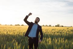 Happy young stilysh buisinesman with rised hand during the sunshine outdoors. Happy buisinesman having fun in summer fields, man in buisines suit enjoy of stock photo