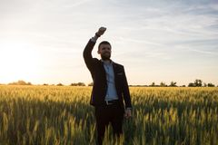 Happy young stilysh buisinesman with rised hand during the sunshine outdoors. Happy buisinesman having fun in summer fields, man in buisines suit enjoy of royalty free stock image