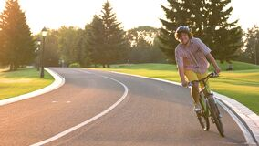 Happy young student cycling outdoors. stock footage