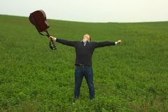Happy young student. On field with guitar stock photo