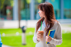 Happy young student girl with a coffee-to-go, walking in a summer park and holding books for reading. Stock Image