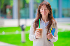 Happy young student girl with a coffee-to-go, walking in a summer park and holding books for reading. Stock Images
