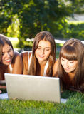 Happy young student girls using a laptop Stock Photography