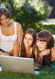 Happy young student girls using a laptop Stock Photos