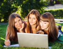 Happy young student girls using a laptop outdoors Stock Images