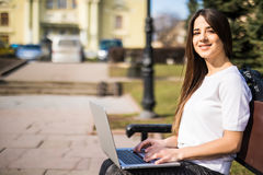 Happy young student with laptop sitting on the bench. Outdoors Stock Photos