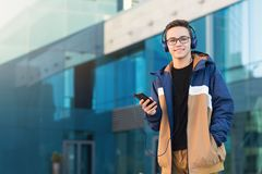 Happy young student listening to music, holding the phone outdoors. Copy space stock photos