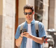Happy young student male texting on his smart phone in modern ci. Young happy student man in jeans denim clothes wearing sunglasses texting on his smart mobile Royalty Free Stock Images