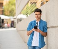 Happy young student male texting on his smart phone in modern ci. Young happy student man in jeans denim clothes wearing sunglasses texting on his smart mobile Royalty Free Stock Image