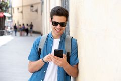 Happy young student male texting on his smart phone in modern city. Young happy student man in jeans denim clothes wearing sunglasses texting on his smart mobile Stock Photo