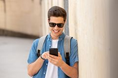 Happy young student male texting on his smart phone in modern city. Young happy student man in jeans denim clothes wearing sunglasses texting on his smart mobile Stock Images